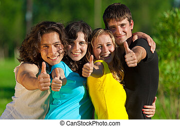 Young group of happy friends showing thumbs up sign together...