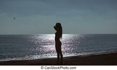 silhouette of young woman on beach on sea background. slow...