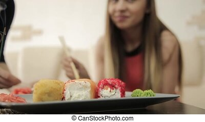 two girlfriends talking during dinner at the restaurant, eating rolls with chopsticks