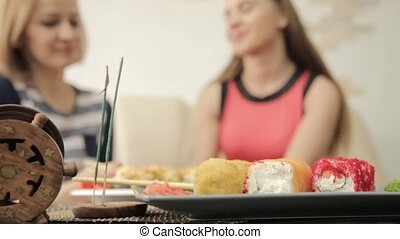 two girlfriends feed each other during dinner at the...