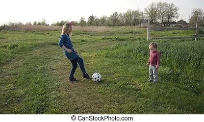 Cute siblings playing football together outdoor