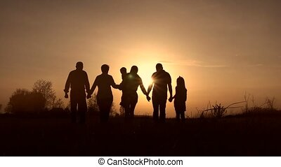 Three generation family walk in meadow at sunset