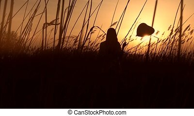Cute girl with balloon standing in cane at sunset -...