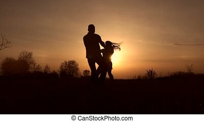 Couple in love whirling on the meadow at sunset -...