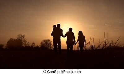 Silhouettes of grandparents with kids at sunset -...