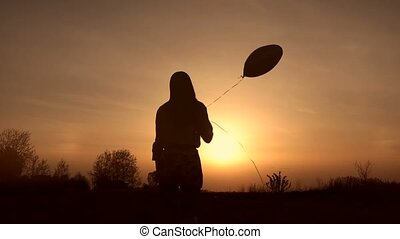 Silhouette of young woman with balloon at sunset -...