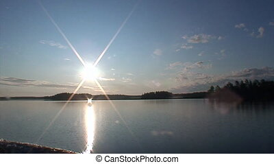Bright rays of sun in sky on background of water in White Sea.