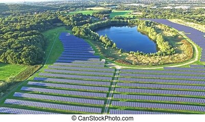 Aerial shot of solar power plant with beautiful lake in the...