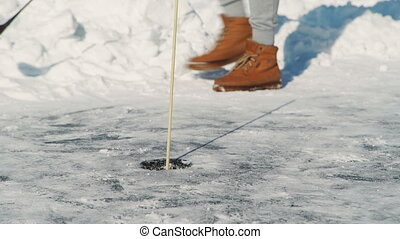 man playing golf on frozen river in nature in winter outdoors