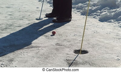 In winter, when playing golf, a man holds a stick and aims...