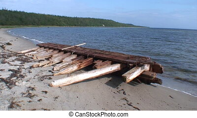 Wreckage of an old wooden ship on the shore of the White Sea.