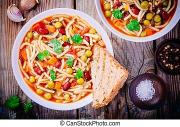 Minestrone soup with vegetables and pasta and whole grain toasts