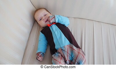 Cute baby lies on the sofa - Happy baby lies on the sofa