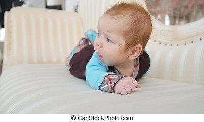 Cute baby lies on the sofa - Happy baby lies on the sofa