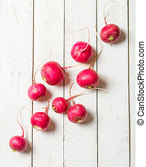 Placer of fresh red radish on a white wooden table. Place...