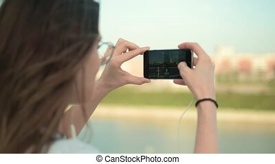 Beautiful summer woman taking pictures on phone 4k -...
