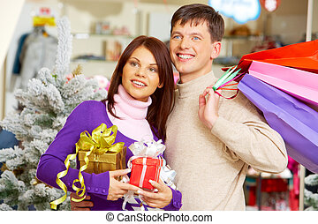 Choosing presents - Image of attractive couple looking aside...