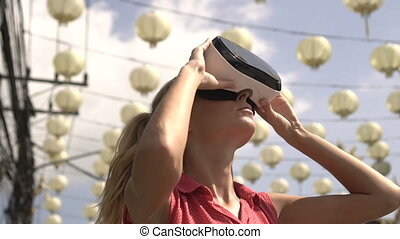 Woman uses virtual reality glasses outdoors