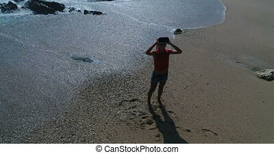 Woman uses virtual reality glasses on the beach - Aerial...
