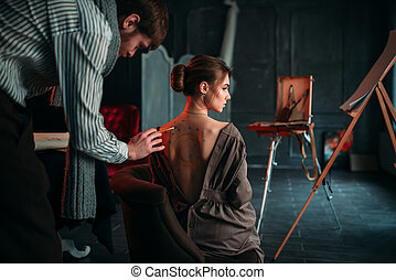 Body painting artwork on womens back. Paintbrush drawing in...