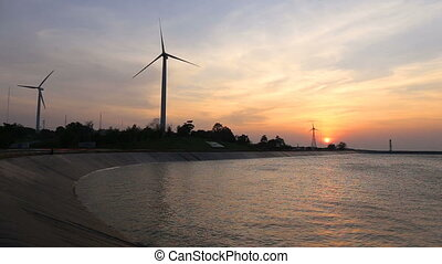 wind turbines creating green energy with reservoir at sunset