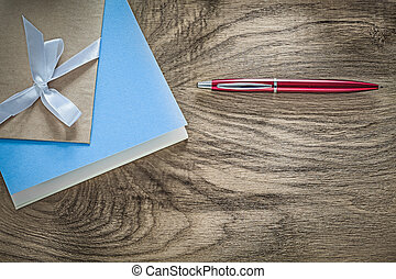 Vintage notepads red biro pen on wooden board top view.