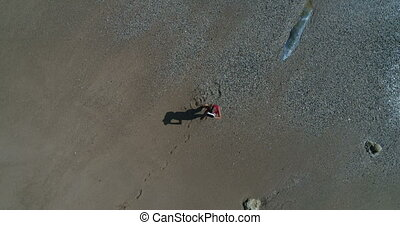 Woman uses virtual reality glasses on the beach - Aerial top...