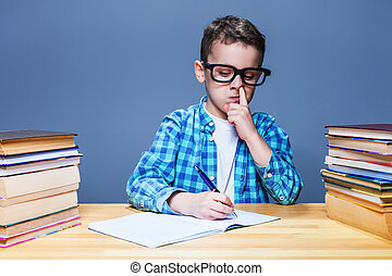Child writing in notebook and picks his nose - Little child...