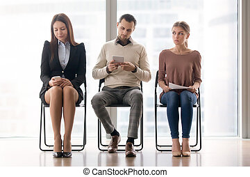 Bored people sitting on chairs waiting for a long time