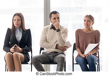 Business people group sitting on chairs waiting, expressing...