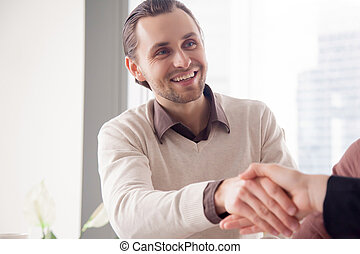 Portrait of smiling handsome businessman shaking female hand on