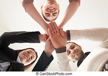 Successful united business team put hands together, view...