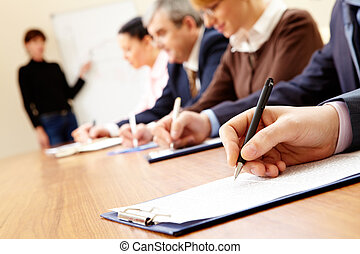 Business training - Close-up of business people writing text...