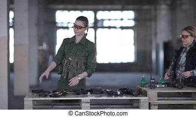 Two girls play airsoft - Two girls run to the table with...
