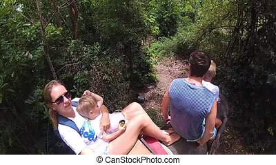 PHANGAN, THAILAND .The family riding on elephants in the tropical forest