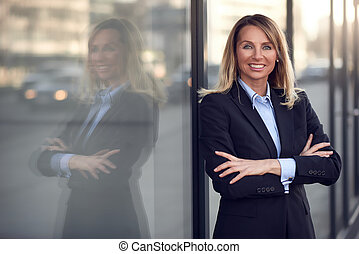 Confident female manager leaning on window