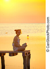 girl reading at the sunset time