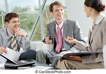 Young businesspeople - Three businesspeople sitting at table...