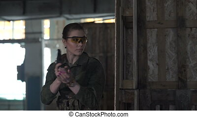 The girl shoots at the enemy - The team plays airsoft in an...