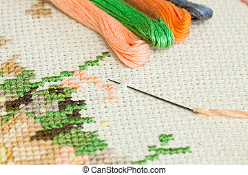 Embroidery. - Closeup of needle put into cross-stitch...