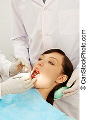 At the dentist - Image of a girl examined by two dentists