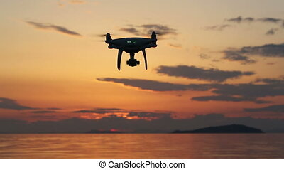 Drone flying against sunset sky