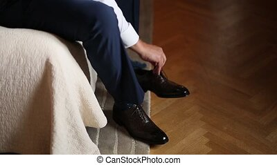 The man in gray slacks and a purple dress socks brown shoes...