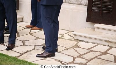 Men legs in shoes and suits on the stone floor