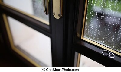 Wedding rings on the window in the rain. Drops on the glass....