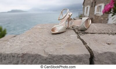 Wedding shoes on the rocks by the sea. Bride Clothing.