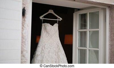 The bride's dress hangs on the cornice on the window.