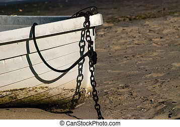 Skiff on the Beach - The white bow of a small boat with...