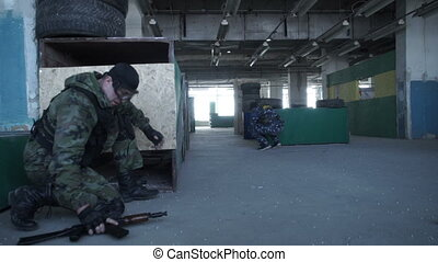 The team plays airsoft - A man is sitting in ambush and...