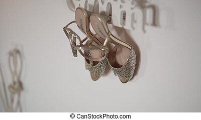 Bride shoes hanging on a plate, bride and groom